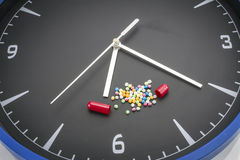 Open red capsule pill with balls color drug on black clock back Royalty Free Stock Photos