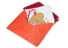 Open red envelope with gingerbread, candy and a gold heart inside . Stock Image