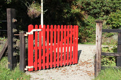 Open red gate leading onto a railway platform Stock Photos
