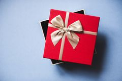 Open red gift with bow on blue background top view. Holidays concept Royalty Free Stock Photography