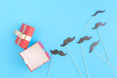 Open red gift box with paper mustaches on blue background stock images