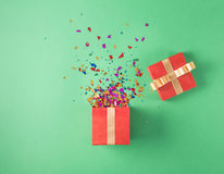 Open red gift box with various party confetti Royalty Free Stock Images