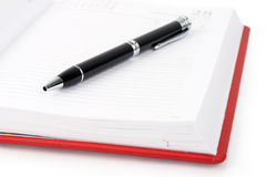 Open red notebook with pen Stock Photo