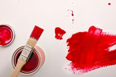 Open red paint canister on white table painted with brush. Open red acrylic paint canister on white table painted with brush. Horizontal composition. Top view stock photos