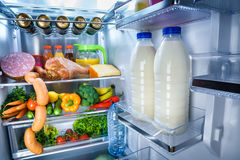 Open refrigerator filled with food. Focus on Bottles of milk in the fridge Royalty Free Stock Image