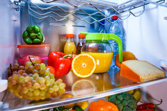 Open refrigerator filled with food Stock Images