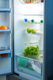Open refrigerator full of food on kitchen Royalty Free Stock Image