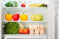 Open refrigerator full of fruits and vegetables stock photo
