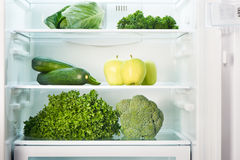 Open refrigerator full of green fruits and vegetables royalty free stock images