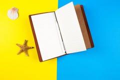 Open reisnotitieboekje, zeeschelpen en zeester over blauwe en gele achtergrond Stock Foto's