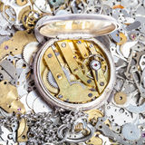 Open retro pocket watch on heap of spare parts. Watchmaker workshop - open retro silver pocket watch with brass clockwork on heap of clock spare parts Stock Images