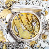 Open retro pocket watch on pile of spare parts. Watchmaker workshop - open retro silver pocket watch with brass clockwork on pile of clock spare parts Royalty Free Stock Image