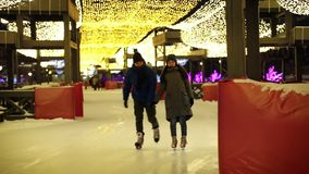 Open rink. Cute young couple ice skating together and having a good time together stock video footage