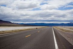 The Open Road. A highway road through the desert in Nevada, beneath a blue sky Stock Photo