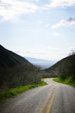 Open road. Empty asphalt road going down middle of valley Stock Photos