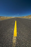 The Open Road. A stretch of wide open highway through the middle of the desert Stock Image