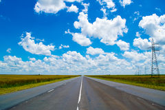 Open road beneath a brilliant blue African sky Stock Photos