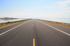 Open road cutting through a lake stock images