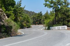 Down a curvy, bendy road. Open road through forest on hillside. Open road. Empty road with no traffic in countryside. Curvy, bendy open road through forest on royalty free stock photos