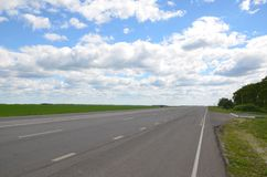 An open road. Going beyond the horizon. The sky with fluffy clouds over the road and field. The long road in biggest country in the world. An immense distance stock photos