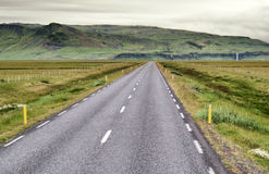 Open road in Iceland. Empty road in Iceland with green mountains at the back Stock Photography