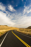 Open Road Scenic Journey Two Lane Blacktop Highway. A well preserved two lane road leads around a bend to an interesting sky Stock Images