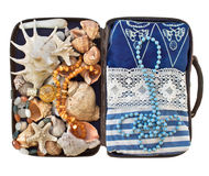 Open road suitcase with clothes and shells Stock Photo