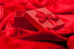 Open rode buitensporige doos op rode zijde Stock Afbeelding
