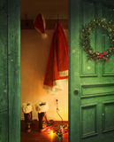 Open rustic door with Santa outfit hanging on hooks Stock Photo