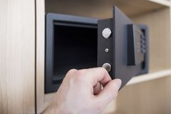 Open safe door with electronic lock close up. Keep money and jewelry at home. man`s hand and safe in the apartment. Open safe door with electronic lock close up Stock Photography