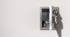 Open Safe On Wall With US Dollars. An open metal safe with bundles of us dollars on a light colored isolated wall background Stock Photography