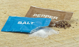 Open salt and pepper sachets Stock Images
