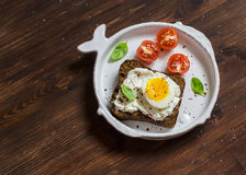 Open sandwich with feta cheese and boiled egg, tomatoes, and basil on a white plate on a wooden surface. Stock Photos