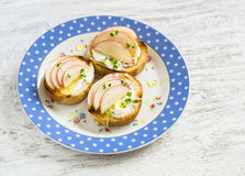 Open sandwich with goat's cheese, apple and honey on a light wooden board. Royalty Free Stock Image