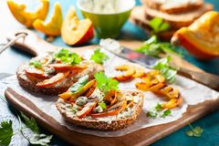 Sandwich with grilled pumpkin. Open sandwich with grilled pumpkin and soft cheese on multigrain rye bread stock photos