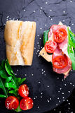 Open sandwich with jamon, arugula, tomatoes, cheese on stone slate black background. Top view.  royalty free stock image