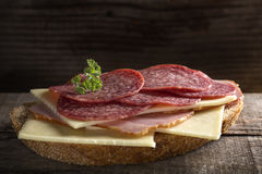 Open sandwich made from cheese, ham and Italian salami on wood Royalty Free Stock Photography