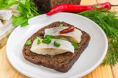 Open sandwich with pickled herring slices on brown bread closeup. Open sandwich made of brown bread and slices of fillet of pickled Atlantic herring on a saucer Royalty Free Stock Images