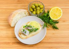 Open sandwich with slices of pickled herring and some ingredient. Open sandwich with slices of pickled herring fillet on a saucer and beside white bread, green stock photography