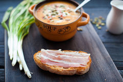 Open sandwich with smoked bacon and pumpkin cream soup Royalty Free Stock Photography