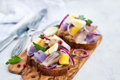 Open sandwich smorrebrod with herring, onion, potato and eggs. Danish open sandwich smorrebrod with herring, onion, potato and eggs Stock Photos