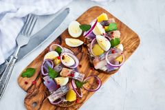 Open sandwich smorrebrod with herring, onion, potato and eggs. Danish open sandwich smorrebrod with herring, onion, potato and eggs Royalty Free Stock Photography