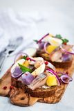 Open sandwich smorrebrod with herring, onion, potato and eggs. On light background Stock Photography