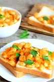 Open sandwiches with baked beans, carrots and parsley on a plate. Baked white beans in a bowl, bread slices Royalty Free Stock Image