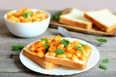Open sandwiches with baked white beans. Beans baked with carrots, garlic and tomato sauce on a bowl Royalty Free Stock Image