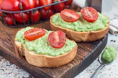 Open sandwich with mashed avocado and cherry tomatoes on toasted bread, sprinkled with black pepper, horizontal. Open sandwiches with mashed avocado and cherry royalty free stock images