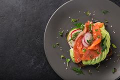 Open sanwiches with dark rye bread, avocado, smoked salmon and r. Adish, black background, top view Stock Image