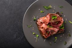 Open sanwiches with dark rye bread, prosciutto and sun dried tom. Atoes, black background, top view Royalty Free Stock Photography