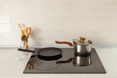 Open saucepan, pan and wooden spoons in modern kitchen with induction stove. Royalty Free Stock Images