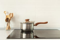Open saucepan and wooden spoons in modern kitchen with induction stove. Royalty Free Stock Photos